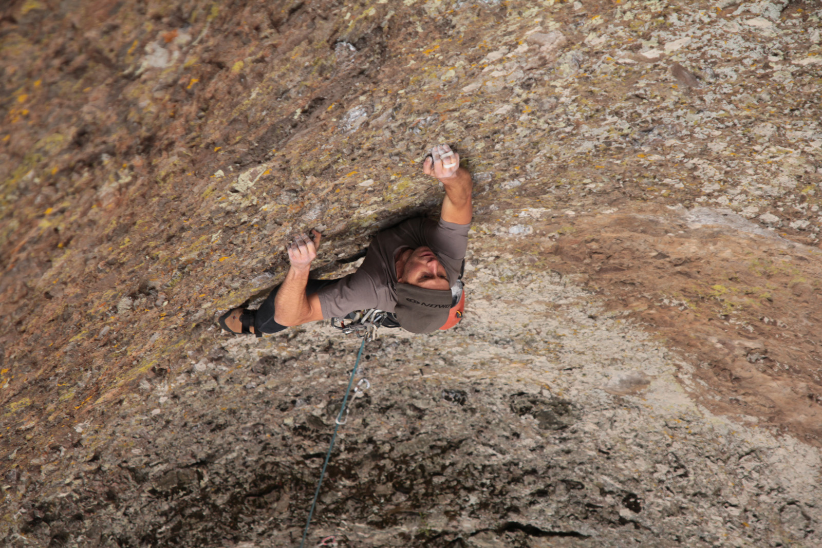 man in grey hat rockclimbing