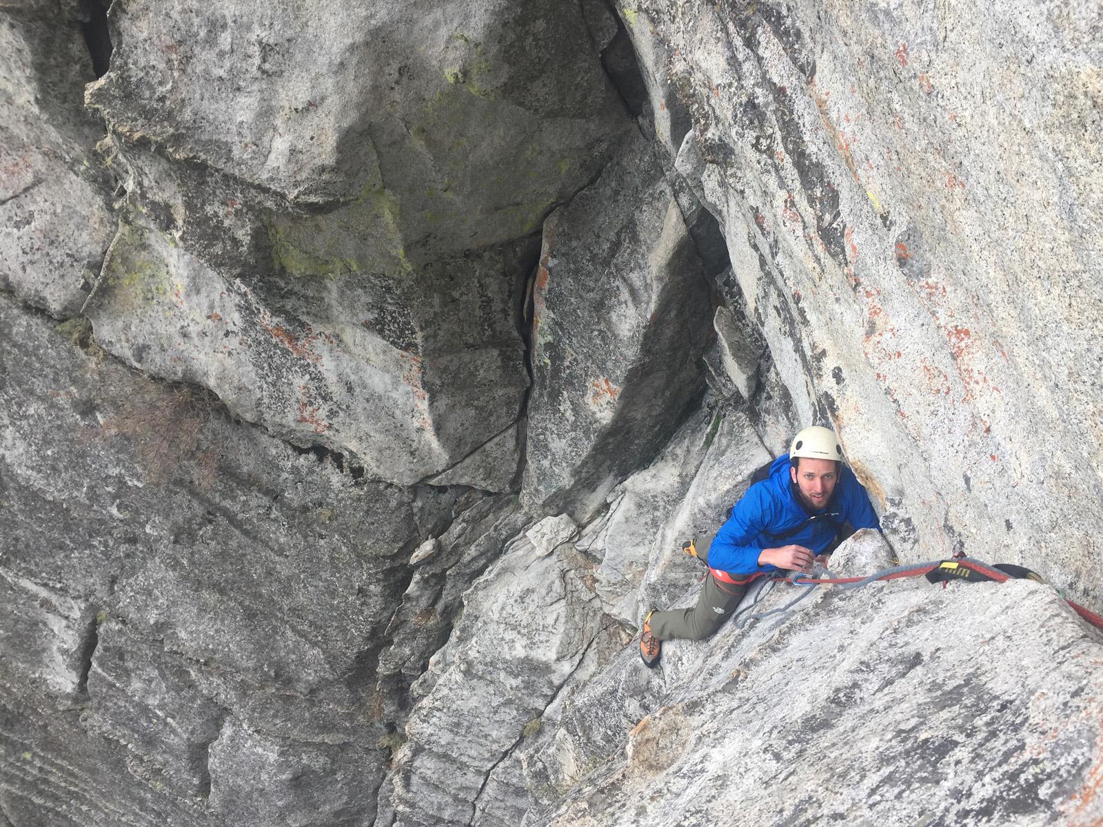 man in blue jacket rock climbing