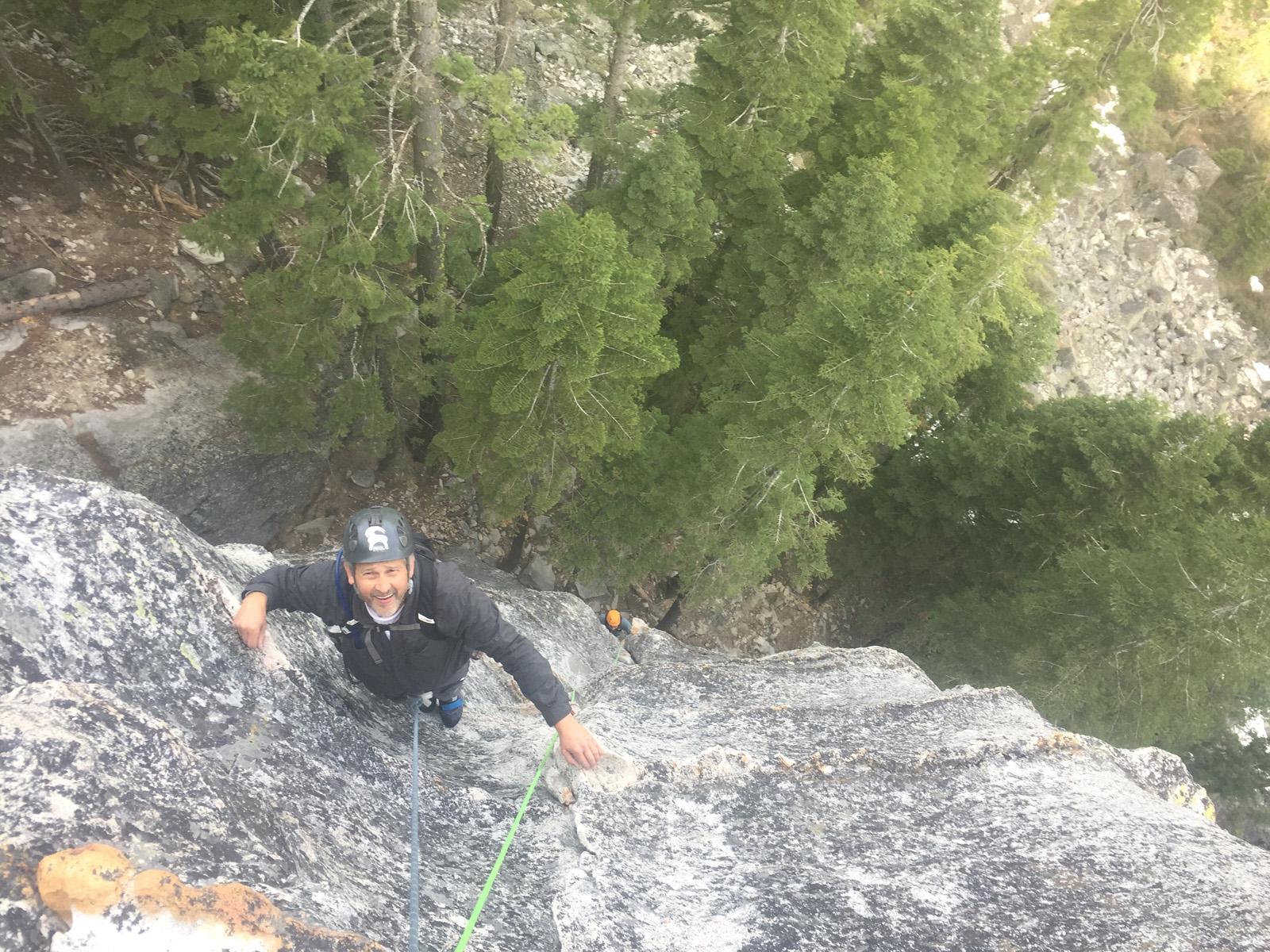 man in black helmet rock climbing