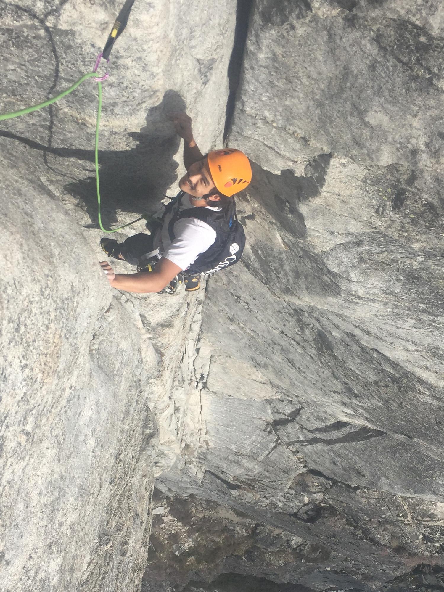 man in orange helmet rock climbing